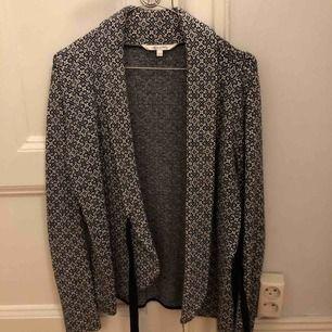 Säljer en kofta med omlott-knytning med svart och grått mönster! Fräscht skick! Möts upp i Stockholm/köpte står för frakt!