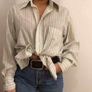 En orangegrönvit randig skjorta från Beyond Retro. Använd ett fåtal gånger. Passar de flesta storlekarna då skjortan är i en större modell. Personen på bilden har knutit den och har storlek XS.  Möts i Stockholm annars står köparen för frakten :)