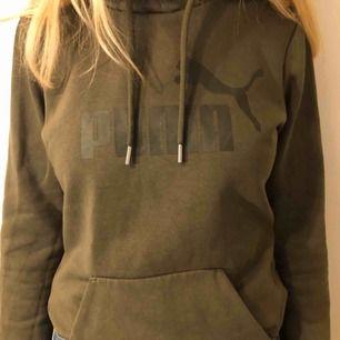 Mörkgrön hoodie med luva och pumamärke. Frakt står köparen för