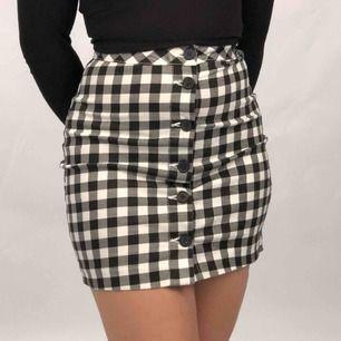 Svart & vit rutig kjol med knappar framtill. Storlek 34 men passar 36 (XS/S) också pga stretchigt material! Frakt ingår i priset!💞