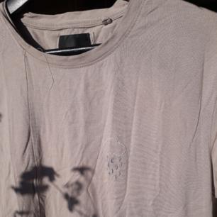 Mysig lång t-shirt med ett broderat måln på. Den är längre på ena sidan. Lite skrynklig men inget som inte går att lösa med ett strykjärn.