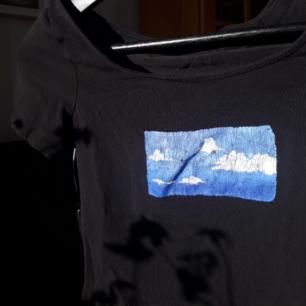 T-shirt med en målad bild på av en himmel med måln.