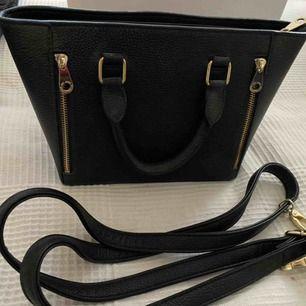Oanvänd don Donna väska med justerbart band som kan sättas på. Väskan är en mindre modell av en stor handväska!
