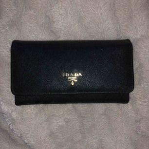 Jättefin prada plånbok jag aldrig använt, och som har ett äkthetskort. Fick den som present och har tappat bort boxen så vet dessvärre inte om den är äkta, kan därför tänka mig att gå ner i pris