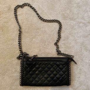 Svarta väska med en silvrig kedja som band och andra silver detaljer. Märke Tiamo. Kan mötas upp i Stockholm annars står köparen för frakt.