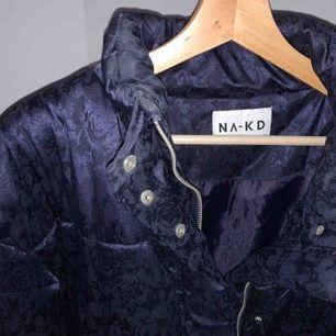 Mörkblåa puffer jacket från NAKD. Svagt blommönster på. Kan mötas upp i Stockholm annars står köparen för frakt.