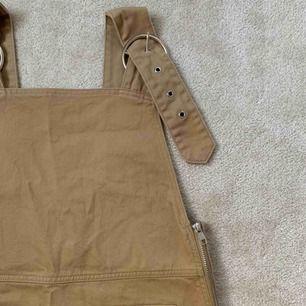Ljusbrun/beige hängsle klänning från Weekday. Aldrig använd! Kan mötas upp i Stockholm annars står köparen för frakt.