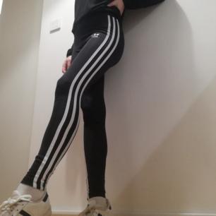 Svarta leggings i typ tjockare bakräktsmaterial (sånt som är lite glansigt) i stl XS. I fint skick köpta för ett år sen och har den nya Adidas logon på benet. Frakt 42 kr.