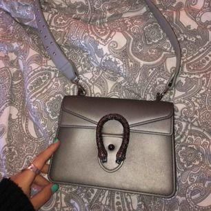 Grå gucci inspirerad väska ( fake ) men väldigt fin!! Använd fåtal gånger därav nyskick.