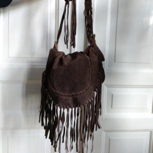Väska från indiska i brun mocka. Skick som på bilder. Frakt på 88 kr tillkommer.