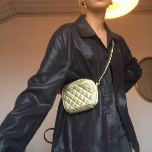 Söt guldig väska med guldkedja! Går att använda som crossbody bag eller one shoulder bag! Själva väskbandet består av guldkedja och det guldiga  väsktyget, den är egentligen längre men jag har knutit det på bilderna!  Möts upp i Stockholm eller skickar!