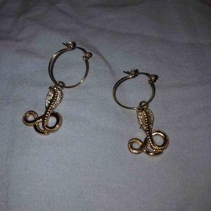 små guldiga hoops med ormar. jättefina och använda max två ggr. frakt är inkl i priset (11kr).