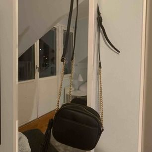 En liten svart axelremsväska med guld detaljer. Aldrig använd