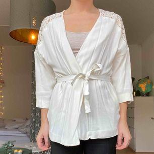 En vit kort kimono med spets på ryggen. Aldrig använd. Storlek XS från HM. Köpt för 499.