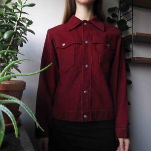 Jättefin manchesterjacka i en djup röd färg. Köpt secondhand och passformen är härligt retro och den passar även bra med tjock tröja under. Storlek S/XS. Kan mötas upp i Göteborg, annars tillkommer 59kr frakt.