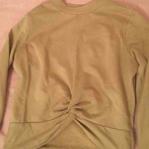 En tröja från H&M i färgen beige. Det är storlek s och det är som den är knuten vid naveln. Men de går inte öppna upp eller något! Utom den är tillverkad så.
