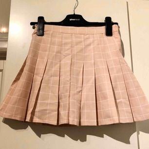 Ljusrosa och vit rutig tenniskjol från koreanska märket Chuu. Har inbyggda shorts, så kjolen funkar att ha när det blåser! Dragkedja baktill. Säljer pga för liten💞 (säljer en likadan i ljusgrå också, kolla min sida!)