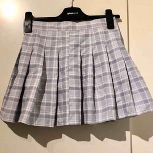 Ljusgrå och vit rutig tenniskjol från koreanska märket Chuu. Har inbyggda shorts, så kjolen funkar att ha när det blåser! Dragkedja baktill. Säljer pga för liten💞 (säljer en likadan i ljusrosa också, kolla min sida!)