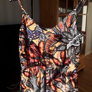 Jumpsuit med ett härligt mönster på. Justerbara band resår i midjan och fickor.