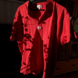 Röd vintage Levi's t-shirt med knappar, två av knapparna är borta men det är inget som stör. Det är lätt att sy dit två nya om man vill.