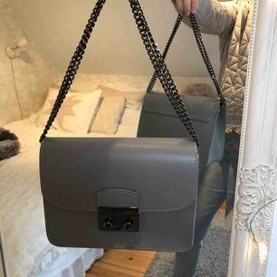 Grå handväska från Chiquelle med långt axelband som man kan göra om. Mycket sparsamt använd!  Köpt för 699kr på Chiquelles hemsida.   Möts upp i Halmstad eller så står köparen för frakten. Betalning sker via swish.