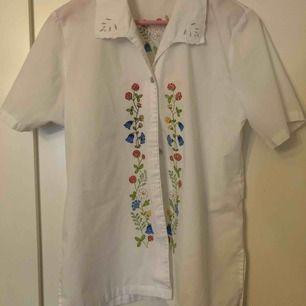 En till fin skjorta med målade blommor på, helt unik och inget som liknar något som jag har sett innan. Ger mig en känsla av midsommar. Alla knappar är där dem ska och inga lösa trådar som jag kan se. (Inte inklusive frakt, det står köparen för!)