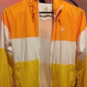 En tunn Nike performance vindjacka i gul, vit och orange colorblock. Riktigt snygg och trendig, nyskick. Köpare betalar frakt på ca 40.