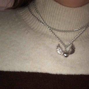 Halsband med hjärtvinge berlock. Silver kedja, går att få med den tjocka silvriga kedjan som finns på min sida!