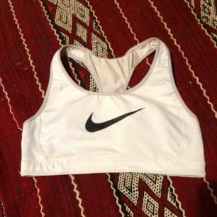 Nike sport-top i stl XS, vit med stor svart logo på framsidan. Som du ser har en tråd där bak släppt lite men tyget har inte gått upp pga det så den är helt intakt annars! Snygg att ha under see-through överdelar. Frakt 42 kr.
