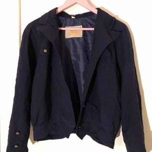 Marinblå jacka i tunt material, perfekt för sommaren med en härlig vintage look. Inga lösa trådar eller knappar som jag kan se. (Inte inklusive frakt, det står köparen för!)
