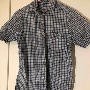 En rutig skjorta i blå, grön och vit med broderade blommor uppe i kragen och knappar i trä. Inga lösa lösa trådar eller knappar som saknas som jag kan se. (Inte inklusive frakt, det står köparen för!)