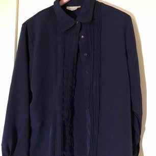 En mörkblå skjorta i tunt material, ger mig en känsla av att vara inspirerad av marinen kanske. Den har detaljer runt kragen och längst med knapparna. Inga lösa trådar eller knappar som saknas som jag kan se.  (Inte inklusive frakt, det står köparen för!)