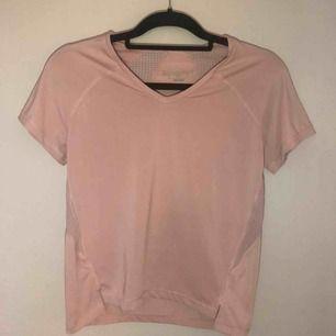 Smutsrosa t-shirt i träningsmaterial med v-ringning. I väldigt fint skick då den endast används 2-3 ggr. Frakt tillkommer :)