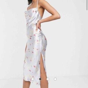 ASOS DESIGN högglansig midi klänning i satin med smala axelband och snörning baktill   Helt ny och oanvänd klänning. Passade inte mig och hann inte lämna tillbaka i tid så säljer vidare men för lite billigare pris:)