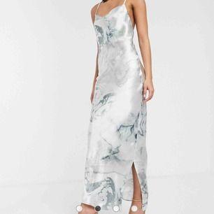 ASOS DESIGN - Högglansig slip-klänning i satin och maximodell med smala axelband och snörning i ryggen  Helt ny och oanvänd klänning. Passade inte mig och hann inte tillbaka i tid så säljer vidare:)