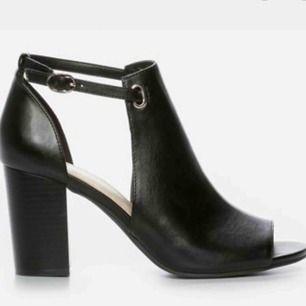 FeetFirst. XIT. Superfin sandal i svart skinnimitation. Tuffa nitar, dekorativa detaljer samt liten klack (7cm). Rem med spänne och justerbar knäppning.  Skorna är så gott som nya, använt dem vid två tillfällen. Säljer pga liten storlek. Nypris 400kr.