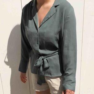 """Skjorta/blus med """"kavaj urringning"""", använd 2 gånger. Knytning i midjan. Jag är 165 och har vanligtvis M på överdelar. Något mer ljus/klargrön i verkligheten. Frakt tillkommer."""