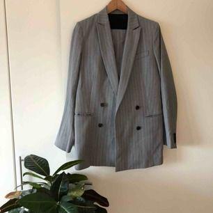 Kritstrecksrandig kostym från J.Lindeberg. Pearl Wool Pin (kavaj) + Kori Wool Pin (byxa). Storlek 38 i kavaj och storlek 36 i byxor.  Använd med i mycket bra skick!  650:- för kavajen. 450:- för byxorna.  900:- för hela kostymen.