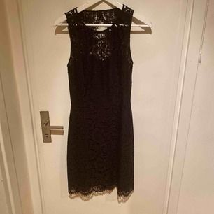 Festklänning i svart spets med öppen rygg. Använd vid ett tillfälle.
