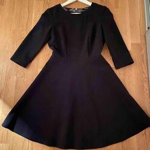 En klassisk svart klänning från Sand Copenhagen med vidd i kjolen och tydlig dragkedja som modern detalj på baksidan. Använd vid fåtal tillfällen så i nytt skick.