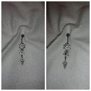 Navelpiercing i kirurgisk stål. Piercingen har en blomma och hänge med droppformad kristall.  ( alla piercings smycken är kokade i saltvatten samt tvättad med piercing sprej ) ( Köparen står för frakten 9kr )