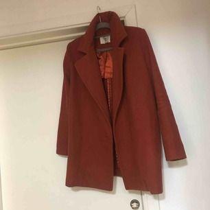 Rostbrun fin kappa utan knappar brukar ha bälte till