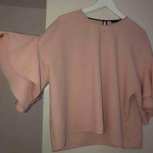 En tröja i ljusrosa med volanger vid armslutning! Passat mig bra såsom är 175cm lång! (Ingen fläck på utan kamera som är dålig) köparen står för frakten💗