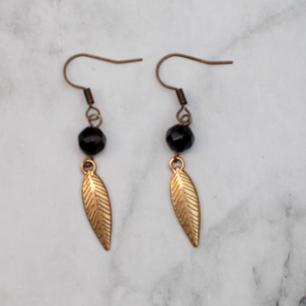 Bronsfärgade örhängen med glaspärlor och löv/fjäder. Nickelfria. Fri frakt vid köp över 100:-.