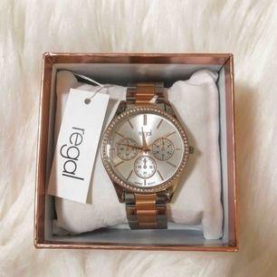 Klocka från märket Regal i roséguld och silver med stenar runt urtavlan. Oanvänd och har endast legat i kartongen som medföljer. Köpt för 498 kr.