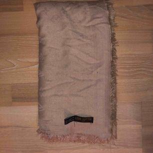 Säljer en FAKE Louis Vuitton halsduk/scarf köpt i Turkiet. Beige med fransar och LV mönster över hela