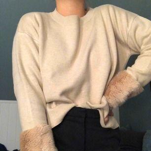 Mysig beige stickad tröja med fake-päls längst ner vid armslut från Lindex märke Holly & White. Sparsamt använd.
