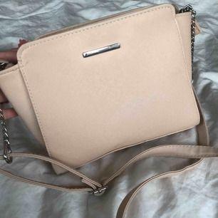 """Axelremsväska i en jätteljus rosa färg, har en liten """"pompom"""" till om man vill ha (väljer man själv såklart"""". Fint skick, knappt använd. Har en inneficka.  Den har fått ett litet märke på underdelen av väskan men det syns inte när man har på sig. (Bild 3)"""