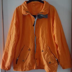 Orange jacka i storlek M. Har en svag svart liten fläck nere på ea ärmen (se bild 2). Fraktkostnad blir 88kr.