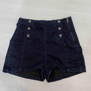 Mörkblåa jeansshorts från Gina Tricot i storlek 36. Bronzbruna knappar och dragkedja på sidan. Säljer pga för små på mig, även därför jag inte har någon bild hur dom sitter på. Köparen står för frakten